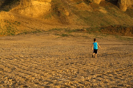 wandering: Little boy wandering alone through wasteland - concept for adventure and exploring - slight motion blur