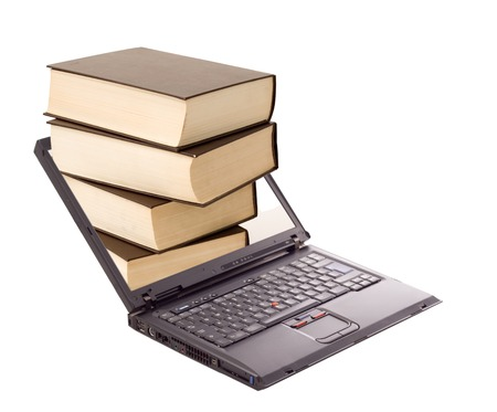 Book stack over laptop - online library and learning concept - isolated Stock Photo