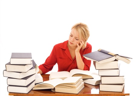Woman at a desk studying with lots of large books - isolated Stock Photo - 1646724