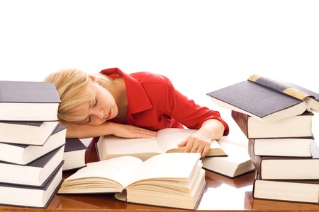 test deadline: Woman asleep on top of her large pile of books - concept for stress, deadlines and overtime - isolated