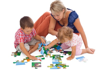 Family, woman and kids, playing with puzzle on the floor - isolated Stock Photo