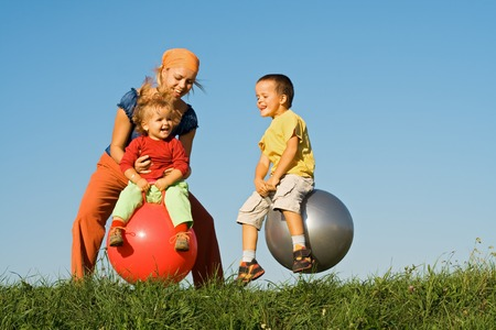 Woman and kids jumping on large balls in the grass under clear blue sky Stock Photo