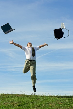 Businessman or office worker throwing away work objects and enjoying the freedom of holiday photo