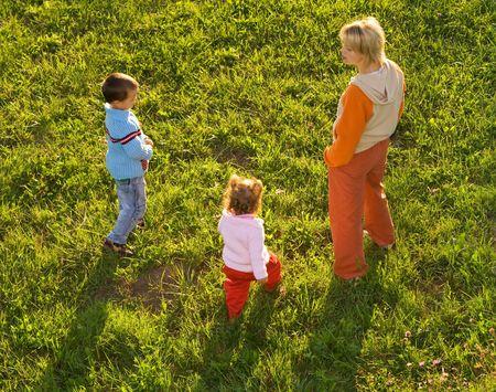 ni�os caminando: La mujer y los ni�os a pie sobre la hierba - calurosa tarde de luces - vista superior