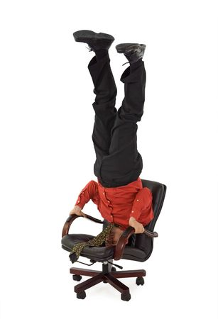 Businessman relaxing office chair standing on his head - isolated photo
