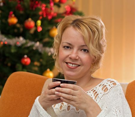 warmth: Woman with coffe or tea cup in front of christmas tree - warmth of the holidays Stock Photo