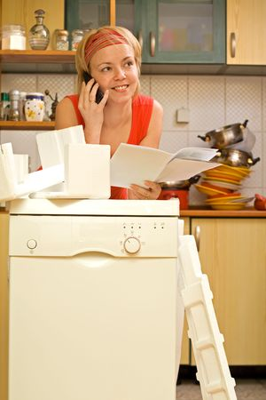 contented: Happy woman on the phone, propping against her new kitchen appliance - a dishwasher