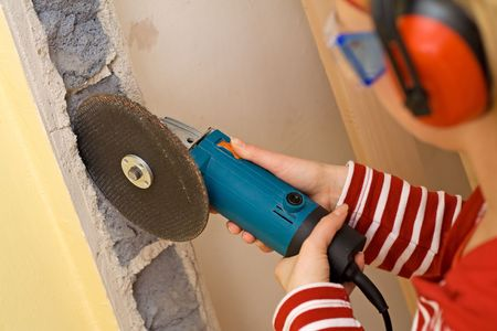 do it yourself: Do it yourself concept - woman with grinder at a jagged wall