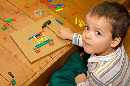 preoccupied: Boy playing on the floor with wooden blocks little nails and a hammer