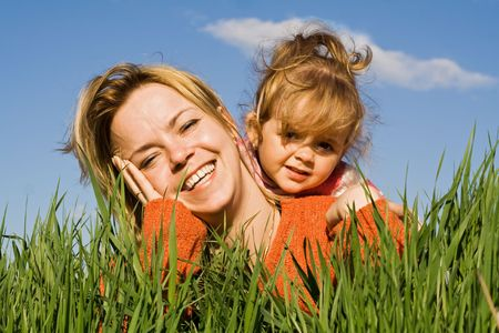 Woman and little girl having fun in the grass photo