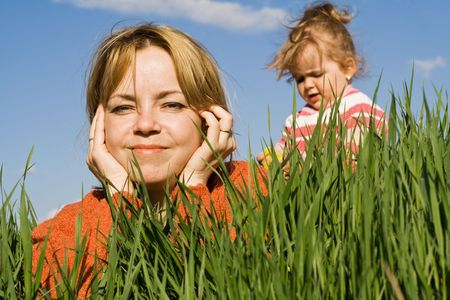 Closeup of a woman and little girl on the green grass field Stock Photo - 2948909