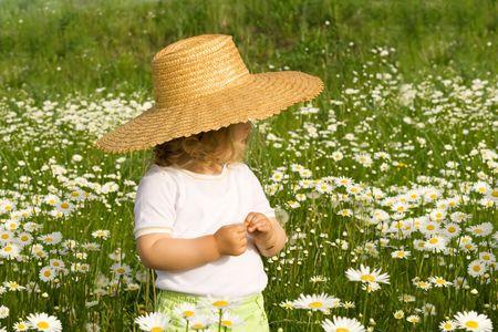 straw hat: Bambina nel campo verde con un sacco di margherite, che indossa un cappello di paglia  Archivio Fotografico