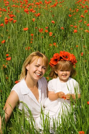Happy woman and little girl among poppies in a green wheat field Stock Photo - 3170053