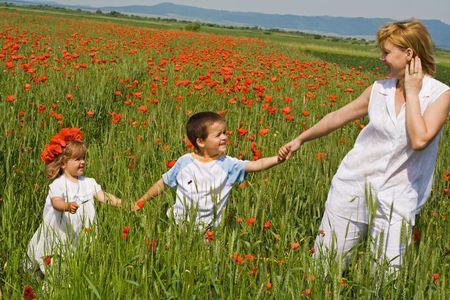 ni�os caminando: La mujer y sus hijos caminando al aire libre entre amapolas  Foto de archivo
