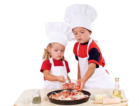 Two kids dressed as chefs preparing a pizza - isolated Stock Photo