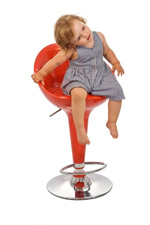Little girl on a red stylish bar stool posing - isolated photo