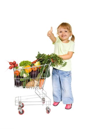 thumbup: Little girl with healthy vegetables in shopping cart showing thumbs up - isolated