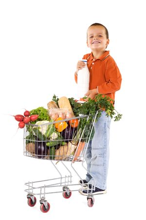 smeary: Happy boy holding milk near a shopping cart filled with groceries - isolated