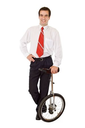 Balance in business concept - confident businessman with monocycle - isolated photo