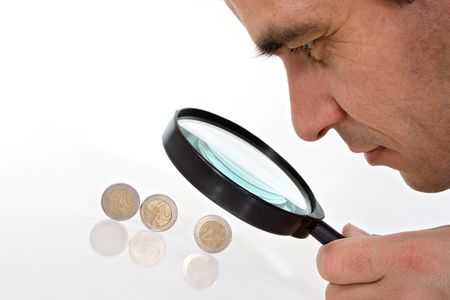 Man with magnifying glass looking closely to euro coins
