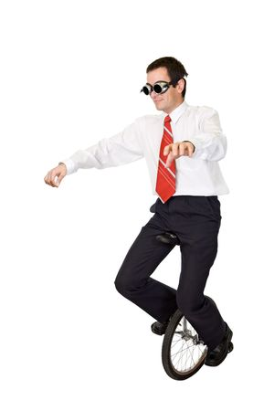 Businessman riding on monocycle - concept for reckless business and risk taking - isolated photo