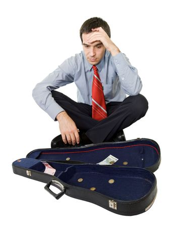 Desperate businessman sitting by a violin case and a few coins - isolated photo