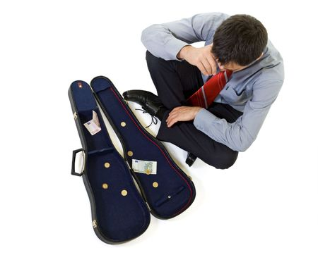 Bankrupt businessman sitting by a violin case with some change - isolated photo