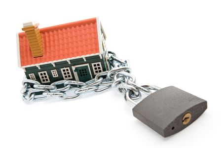 business protection: House in chains locked with padlock - mortgage and foreclosure concept