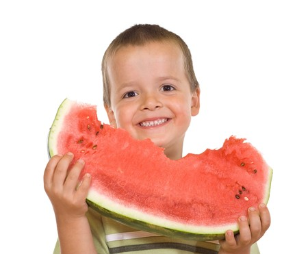 Boy with a large grin holding a watermelon slice - isolated photo