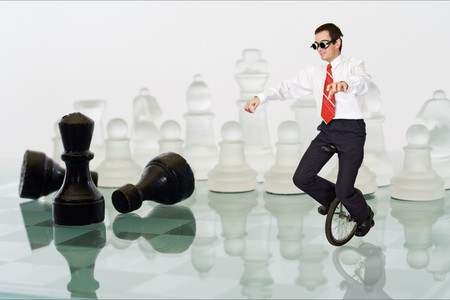 Businessman keeping his balance riding a mono cycle on a chess board photo