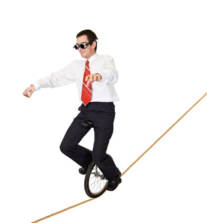Businessman riding on monocycle on a rope - concept for reckless business and risk taking - isolated photo