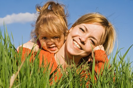 Happy woman and little girl laying in the fresh spring grass - closeup photo