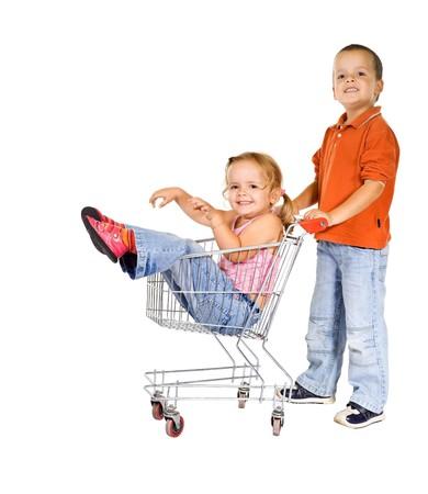 ni�o empujando: Felices los ni�os riendo con la cesta de la compra - aisladas