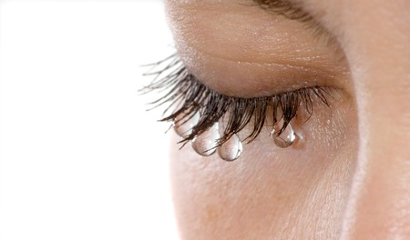 Womans eye with several teardrops hanging on her eyelashes - isolated Stock Photo
