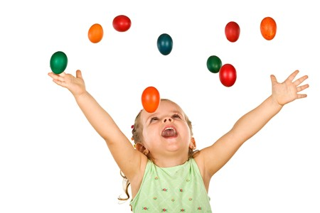 Happy shouting little girl welcoming the falling easter eggs - isolated, without motion blur photo