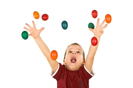 Happy boy shouting and reaching out for the falling colorful easter eggs - isolated, without motion blur photo