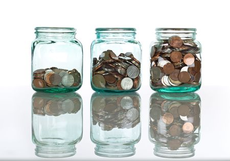 Glass jars with coins on reflective surface, isolated - savings concept