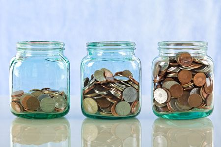 Saving money concept - coins in old jars on reflective surface against blue background photo
