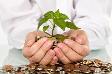 Businessman holding plant sprouting from a handful of coins - good investment and money concept Stock Photo