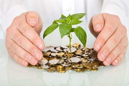 Protecting a good investment and making money concept - businessman hands with plant sprouting from a pile of coins Stock Photo