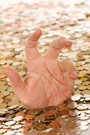 agonizing: Drowning in debt concept - man hand trying to get a grasp, covered in coins