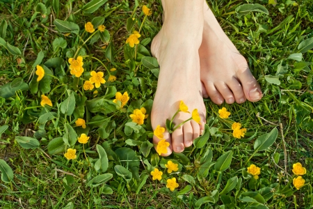 fleurs des champs: Femme repose ses pieds dans la fra�cheur de la v�g�tation au printemps sous le soleil