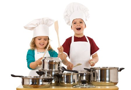 banging: Happy kids dressed as chefs making noise with the cooking pots and wooden spoons - isolated