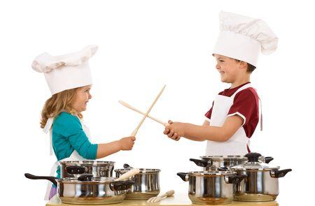 niños cocinando: Chico chefs se divierten duelos con cucharas de madera - aislados Foto de archivo