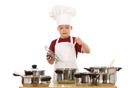 Young kid dressed as a chef preparing a meal - isolated photo