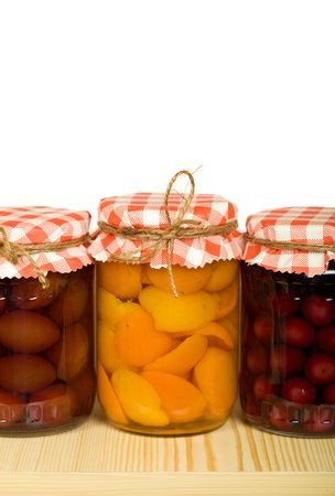 Homemade canned fruits in jars on the shelf - isolated Stock Photo - 5000196