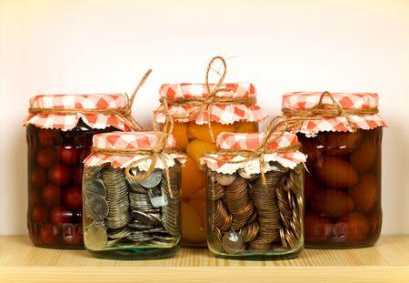 frutta sciroppata: Concetto di risparmio con le conserve di frutta e delle monete in vasi di vetro sulla mensola Archivio Fotografico