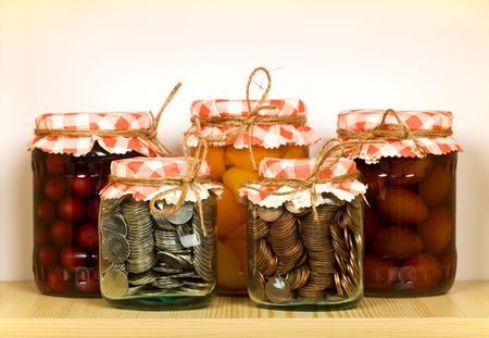 Savings concept with canned fruit and coins in glass jars on the shelf photo