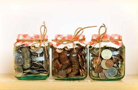 put away: Saving money concept with coins put away in glass jars on a shelf Stock Photo