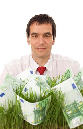 Businessman with euro banknotes in grass - green business concept, isolated photo